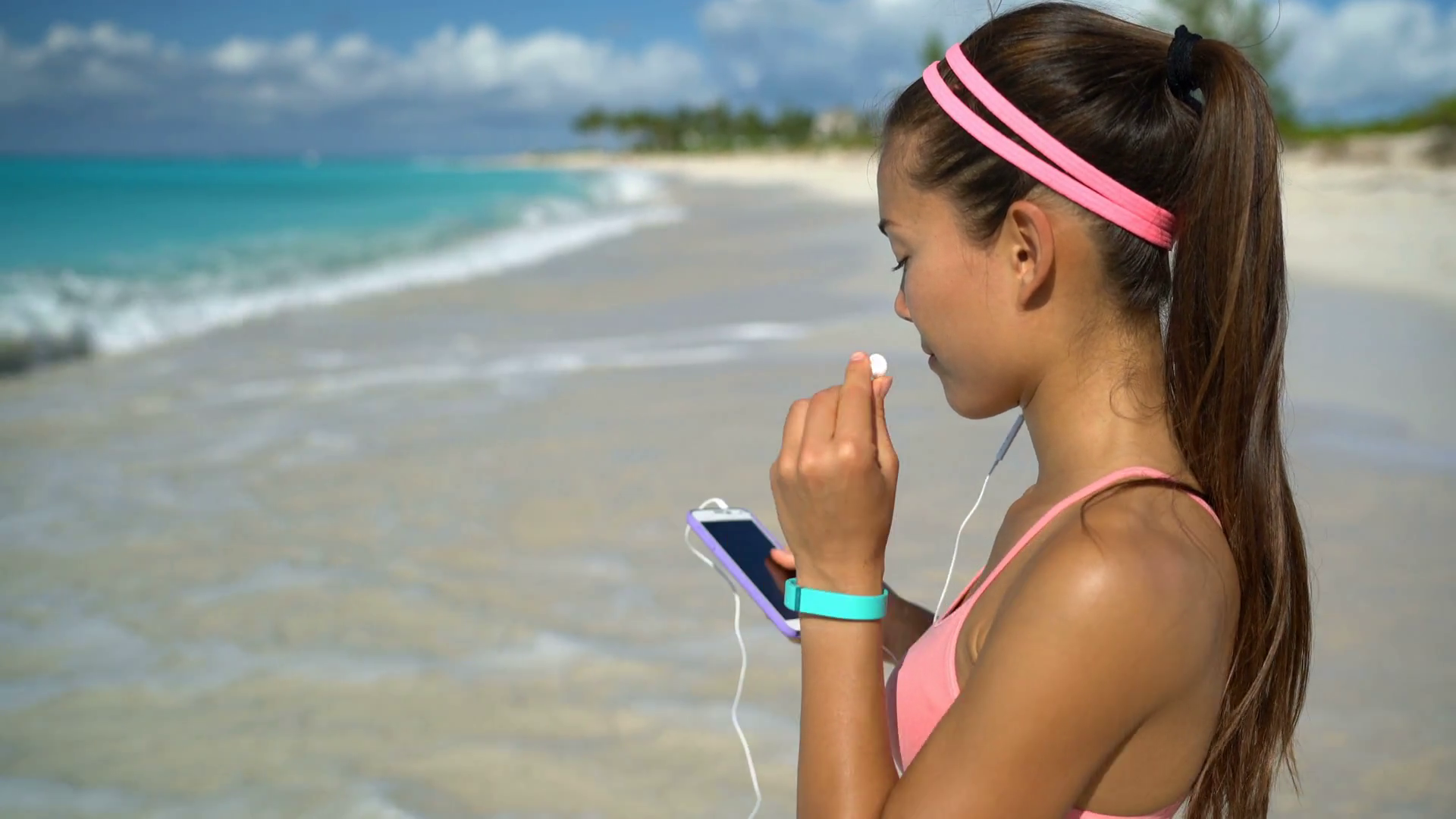 woman-listening-to-music-running-exercising-on-beach-young-woman-putting-earphones-in-ear-getting-ready-to-run-on-sea-shore-female-fitness-girl-training-listening-music-while-jogging-on-sunny-day_hz0ah_-fx_thumbnai